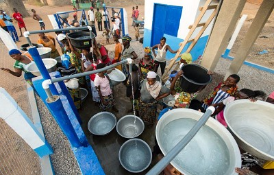 People gathering and filling large metal water buckets from several faucets - Nyani Quarmyne/ Panos
