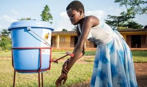 African lady washing her hands from a raised blue bucket with a spout