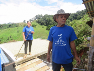 Man and woman working on structure while wearing 'Manos al Agua' t-shirts